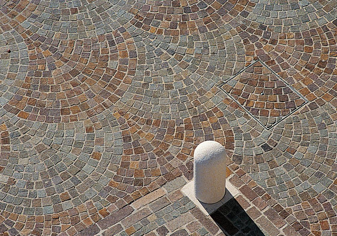 Pavimentazione con posa di cubetti in porfido a coda di pavone in due colori, perfettamente eseguita con corrispondenza tra ogni singola arcata e i cubetti di riempimento