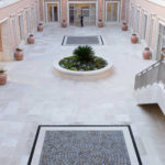 A view of a pation with travertine tiles and porphyry cubes